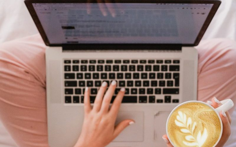 Lady enjoys a coffe whilst using a laptop